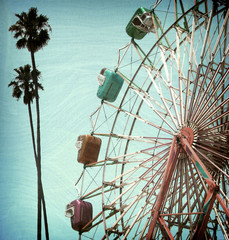 aged and worn vintage photo of ferris wheel and palm trees