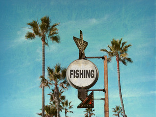 aged and worn vintage photo of fishing sign at beach