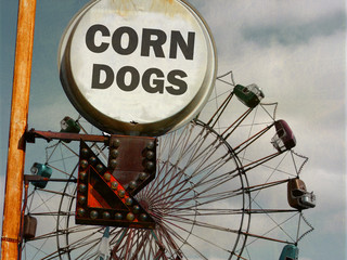 aged and worn vintage photo of corn dog sign at fair with ferris wheel