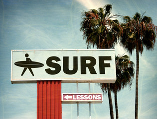 aged and worn vintage photo of surf lessons sign on beach