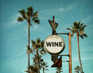 aged and worn vintage photo of wine sign on beach with palm trees