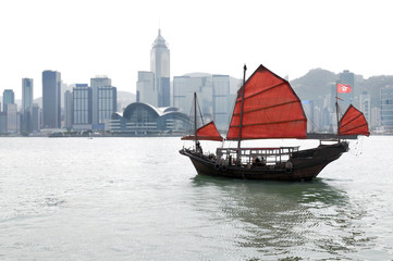 Hong Kong city skyline with traditional sailing boat and red sails