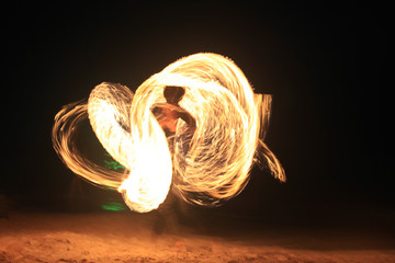 Fire-dancing in slow speed shutter photography on the beach