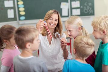 schüler in der grundschule untersuchen eine flüssigkeit im reagenzglas