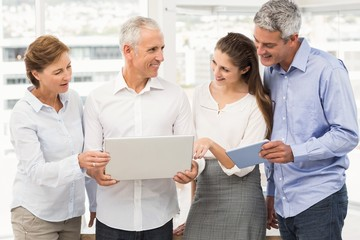 Smiling business people using laptop