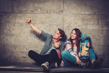 Young couple with skateboard  taking selfie outdoors