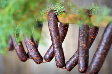 Südtiroler Kaminwurzen zur Trocknung aufgehängt, frischer Wacholder als Deko