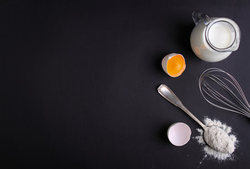 eggs, flour, milk and whisk on a dark background