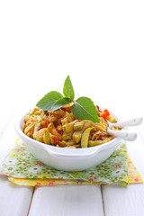 zucchini in a white plate with a fork decorated with basil