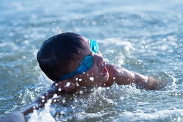 Ten year old boy teenager swims in the sea