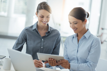 Business women working together on a tablet