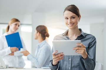 Smiling business woman using a tablet