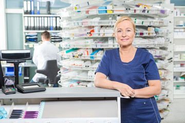 Smiling Pharmacist Leaning At Cash Counter In Pharmacy