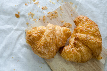 Croissant ,Bread crumb on wooden board and tablecloth
