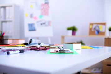 Desk of an artist with lots of stationery objects. Studio shot
