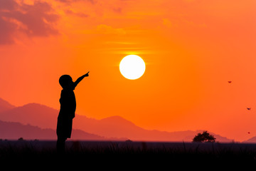 silhouette of asian little boy point to the sun at sunset backgr