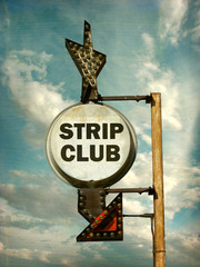 aged and worn vintage photo of strip club sign