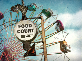 aged and worn vintage photo of food court sign at carnival