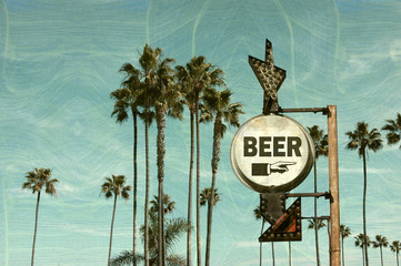 Aged and worn vintage photo of beer sign on beach with palm trees