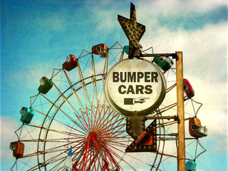 aged and worn vintage photo of bumper cars sign at carnival with ferris wheel
