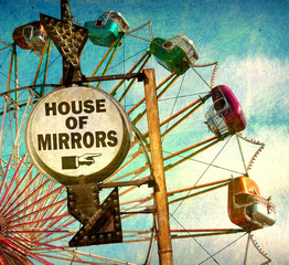 aged and worn vintage photo of house of mirrors sign at carnival