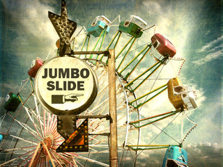aged and worn vintage photo of jumbo slide ride sign at carnival
