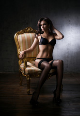 Beautiful and sexy girl in underwear sitting in a vintage armcha