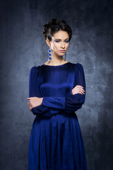 Young and beautiful fashion model posing in a blue dress