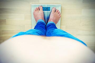 Übergewicht - Mann mit Bauch auf einer Waage