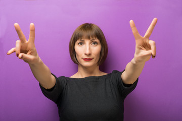 portrait of a woman showing victory sign on a purple background