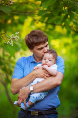 Dad with a baby boy in his arms, close-up, summer