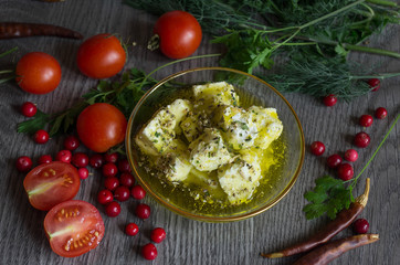 feta cheese in olive oil and herbs on a wooden table surrounded