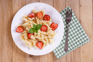 Pasta with strawberries on a plate on the oak table. Napkin with a fork. Top view.
