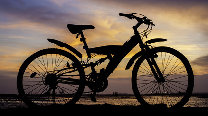 Silhouette of mountain bike with sunset sky beside sea