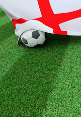 Soccer ball and national flag of England,  green grass