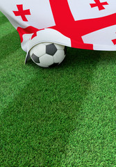 Soccer ball and national flag of Georgia,  green grass