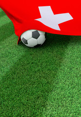 Soccer ball and national flag of Switzerland,  green grass
