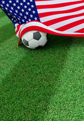 Soccer ball and national flag of USA,  green grass