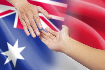 Helping hands with australian and indonesian flags