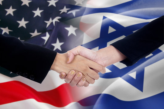 People handshake with the american and israel flags