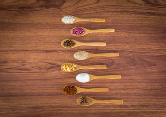 spice and herb in spoons on wooden background.