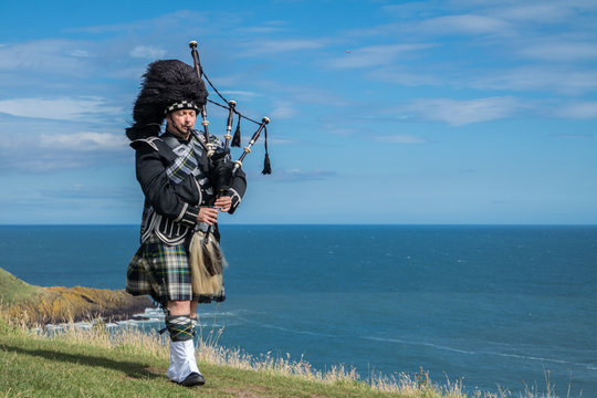 Traditional scottish bagpiper in full dress code with the sea in background