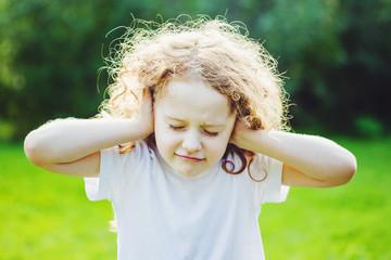Little girl covering her ears.