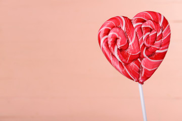 Bright lollipop in shape of heart on wooden background