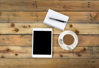 smartphone, tablet and coffee cup with financial documents on wo