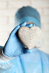 Doctor holding decorative stone heart on brick wall background