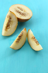 Slices of ripe melon on wooden table close up
