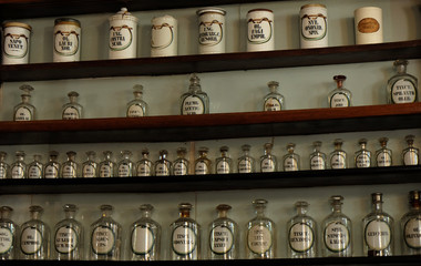 Empty glass bottle and jars on wooden shelves in shop