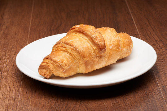 Fresh french croissant on white ceramic plate on dark wooden table background