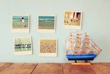 instant photos hang over wooden textured background next to decorative boat